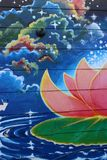 Bright and colorful street art seen on exterior of old building, Woodstock, New York, 2019. Bright and colorful lotus flowers, lily pads, and blue sky seen as royalty free stock image