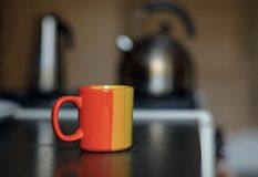 Bright colorful mug. Cup on the kitchen closeup. kettle and coffee pot in the background in defocus. stock image