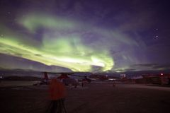 Bright colorful northern lights in the night sky. Helipad and meteorological station. Antarctic. royalty free stock images