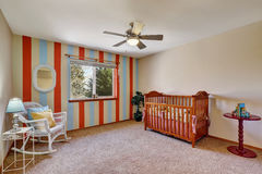 Bright colorful nursery room with contrast striped wall. The room is furnished with a crib, wicker rocking chair and a small table. Northwest, USA stock photos