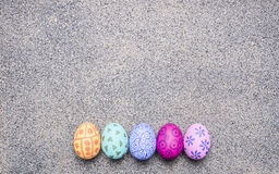 Bright, colorful painted eggs for Easter, laid out in a row border place for text  granit rustic background top view close up Royalty Free Stock Photography