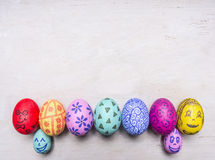 Bright, colorful painted eggs for Easter, laid out in a row border place for text  wooden rustic background top view close up Stock Photo