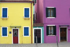 Brightly colored painted houses in yellow, pink & purple with red shutters in Burano Venice Italy Stock Photography