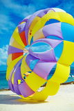 Bright colorful Rainbow Parachute on the beach behind blue ocean Stock Photography