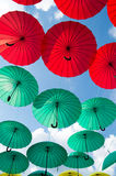 Bright colorful red and green umbrellas background. Against cloudy sky at sunny day Stock Images