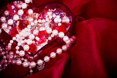Bright colorful stones and pearl in heart Stock Image
