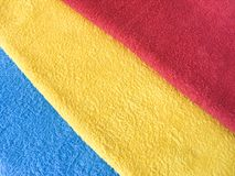 Bright colorful textile background. Terry towels. Bright colorful textile background. Yellow, red and blue, cotton Terry towels Stock Photography