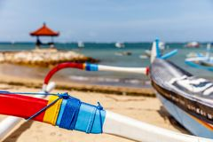 Traditional Indonesian outrigger style wooden fishing boat jukung on the beach at Sanur, Bali, Indonesia. stock photo