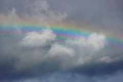 Bright colorful wide  rainbow after the storm in the gray sky. Stock Photos