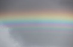 Bright colorful wide  rainbow after the storm in the gray sky. Stock Image