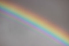 Bright colorful wide  rainbow after the storm in the gray sky. Royalty Free Stock Photo