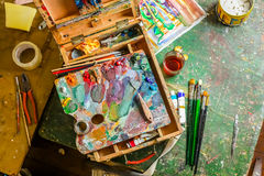 Bright Colorful workplace of the artist with brushes and oil paints Stock Images