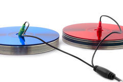 Bright colors of digital sound. S: red and blue compact discs with headphone and microphone cords Royalty Free Stock Photos