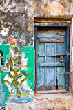 Bright colors of Indian street life. South India, Tamil Nadu. Bright colors of Indian street life. Colorful composition with old  blue door and cracked religious Royalty Free Stock Photography