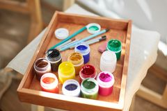 A top view of the objects for drawing. Brushes, paints in a box for materials on wooden parquet. Art concept. Bright colors of oil paints for drawing in a Stock Photo