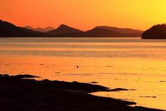 Colourful Sunset over Tumbo Channel, Gulf Islands National Park, Saturna Island. The bright colors of the sunset highlight the array of mountains on Saturna Stock Photo