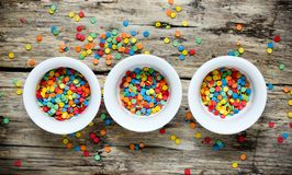 Bright coloured confetti sugar sprinkles. In white bowls on wooden background top view Royalty Free Stock Image