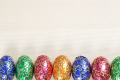 Bright coloured easter eggs. A row of bright coloured easter eggs at the bottom of the page. Wood grain on the rest of the page Royalty Free Stock Images