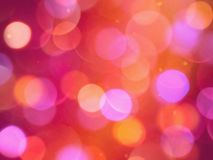 Bright coloured round blurred lights on a glowing warm red background. A bright coloured round blurred lights on a glowing warm red background stock photos
