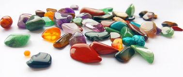 Bright coloured semi precious gemstones and gems. Assorted natural bright coloured semi precious gemstones and gems on white background for design and decoration royalty free stock photos