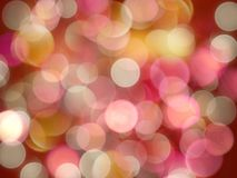 Bright coloured yellow and pink round blurred lights on a glowing red background stock photo