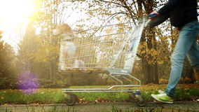Bright colourful footage of a man carrying his dog in the supermarket trolley stock footage