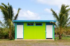 Bright colourful restroom facility Oahu, Hawaii. With lime green wooden walls and dooors for men and women flanked by two tropical palm trees Stock Images