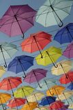 Bright colourful umbrellas hanging on the cords Blue sky background stock images