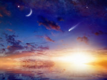 Bright comet, stars and crescent in sunset sky with reflection i Royalty Free Stock Photo