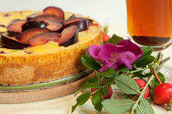 A bright composition with a fruit pie, a glass cup of tea, a fresh dog rose and hips Stock Images