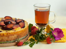 A bright composition with a fruit pie, a glass cup of tea, a fresh dog rose and hips Royalty Free Stock Images