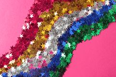 Bright confetti in shape of stars on pink background. Close up stock image