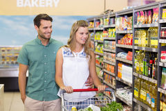 Bright couple buying products in aisle Stock Image