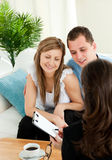 Bright couple concluding car contract with dealer. Bright couple concluding a car contract with a female dealer in the living room Stock Photography