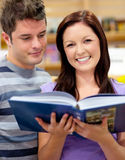 Bright couple of students reading a book Royalty Free Stock Image