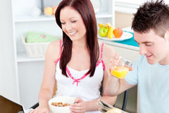 Bright couple using a laptop while breakfast Stock Photos