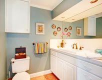 Bright cozy bathroom with white wood cabinets Stock Image