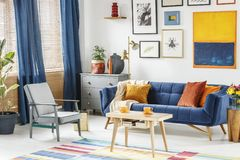Bright and cozy living room interior with blue drapes, a sofa wi. Th orange cushions, gray armchair and a wooden table with two cups of coffee. Real photo Royalty Free Stock Photos