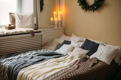Bright cozy modern bedroom with holiday decoration. Bed with grey bedding set and knitted pillow on it, wooden rack. Beautiful royalty free stock image
