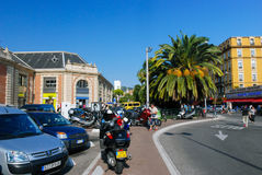 Bright cozy street filled with cars and bikes in Nice, Azure coa Stock Photos