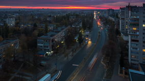 Bright crimson red sunset in the city, traffic of cars, light up lights, lights of houses. In Chernihiv, Ukraine, Timelapse, 4K footage stock video footage