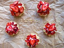 Bright cupcake with strawberries lies on craft paper, the inscription I love you Royalty Free Stock Photography