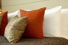 Bright cushions against white pillows. Royalty Free Stock Photos