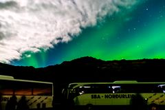 Tour Buses at Aurora Borealis or Northern Lights in Reykjavik, Iceland royalty free stock photo