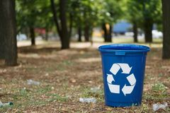 Colorful recycling bins on a natural background. Containers for garbage recycling. Environment, ecology, recycling. A bright dark blue recycling bin in the park Stock Image