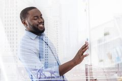 Intelligent worker standing near the magnet board. Bright day. Close up of joyful intelligent worker standing near the magnet board while looking at it with Royalty Free Stock Image