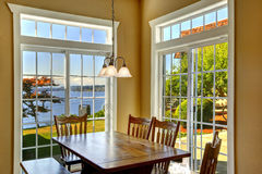 Bright dining area with rustic table and french windows Royalty Free Stock Photo