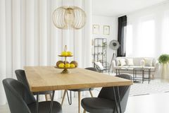 Wooden table in dining room. Bright dining room interior with fruit on wooden table, gray chairs and tubes wall. Living room in the background Royalty Free Stock Photo