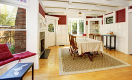 Bright dining room in red walls and white wooden trimmings. Royalty Free Stock Photo