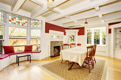 Bright dining room in red walls and white wooden trimmings. Stock Images